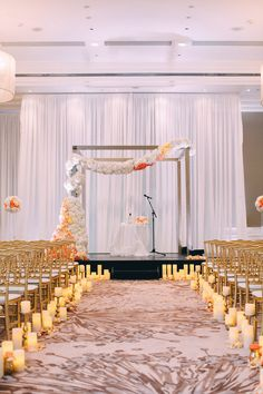 Beautiful ceremony  with white, gold, and peach. Aisle lined with Candle Impressions flameless LED candles leading up to gorgeous floral garland.