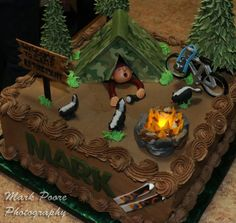 """Camping theme retirement cake. Everything edible. The tent is gum paste covered with camo design sugar sheets. The bike, camera and skunks are also gum paste. The """"Camper"""" was sculpted with fondant. I used a flickering tea candle covered with fondant rocks for the campfire and added royal icing """"Flames."""""""
