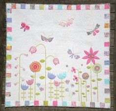 This makes me smile!   This lap quilt (109cm x 109cm) uses fusible web & machine blanket stitch to attach the applique. A simple machine embroidery stitch is used to complete the stitching detail.