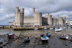 Caernarfon Castle a medieval fortress in Caernarfon,Gwynedd,north-west Wales.Was motte-and-bailey castle in town from late 11th century until 1283 when King Edward I of England began replacing it with current stone structure.Edwardian town and castle acted as administrative centre of north Wales and as result defences built on grand scale.Deliberate link with Caernarfon's Roman past-nearby is Roman fort Segontium-and castle's walls reminiscent of Walls of Constantinople.