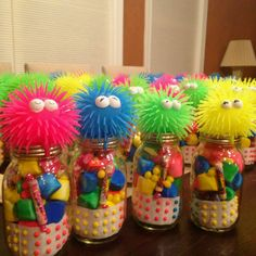 Birthday party favors! Neon marshmallows, buttons, old school candy with toys on the top of Mason jars!