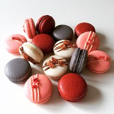 Grey macarons with Oreo buttercream. Red velvet macarons with chocolate ganache. Pink macarons with strawberry buttercream and freeze dried strawberries. White macarons with maple buttercream and crispy bacon.