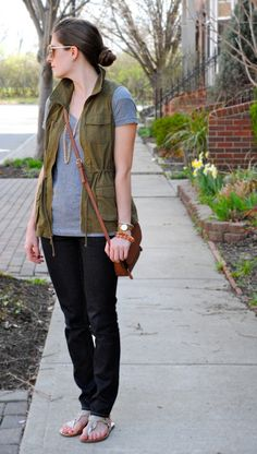 Gray tee, olive vest, black skinny pants