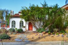 Another Spanish style home with a delightful dry garden features a wide variety of succulents and drought-tolerant plants. Slabs of natural cut stone lead ... Spanish Landscaping, Front Yard Landscaping, Landscaping Ideas, Mediterranean Front Doors, Spanish Style Homes, Spanish Colonial, Spanish Garden, Orange Door, Green Windows