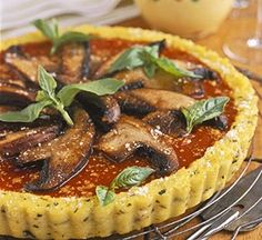 Polenta, seasoned with fresh basil and garlic, serves as the crust in this elegant make-ahead appetizer tart. Make and chill the polenta up to one day ahead. Just before baking, top with portobello mushrooms, tomato sauce, and Parmesan cheese.