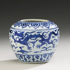 A SMALL BLUE AND WHITE 'DRAGON' JAR  JIAJING MARK AND PERIOD of ovoid form, painted around the body with two five-clawed dragons chasing 'flaming pearls' amidst stylized flames, between a band of petals around the foot and linked ruyi heads on the shoulder, the base with six-character mark within double circles, neck ground down