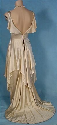 """c. 1930's Ivory Silk Charmeuse Wedding Gown! No decoration. Just simply amazing in the construction of design. The low back is to die for. The overskirt draping... be still my heart. The little attached capelet which still allows the shoulders to show. A masterpiece! Excellent condition, just needs some hooks and eye sewn at the back waist. Has an inner band like a 1920's bra for a tiny bit of support. Measures: 33"""" bust, 25"""" waist, 53"""" long from shoulder to hem in front with train in back."""