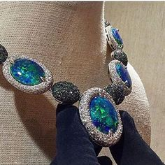 Only way to handle the world's rarest opals... 87.78ct black opal necklace with 16ct white diamonds and 17ct green diamonds. #faraonemennella #blackopal #diamonds #couture #blackgloves