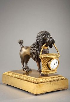 Empire Mini Poodle Clock original pendulum in gilded and patinated bronze of the imperial era. The dog is brown bronze. It holds in its mouth a basket ormolu containing the movement of white enamel dial. The whole rests on a base in gilded bronze palmettes.