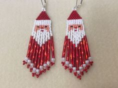 Name:  Santa Dangles Beaded Earrings Size: 3 1/4 inches long ( with hooks) 3/4 inch wide Colors: Winter white, red, peach, black. Vintage twisted red bugle beads   I have been beading for 20 years and I hope my experience shows through my work. For me, this is soul satisfying work and I hope my creations carry within it the energy and love I have put into them. I only use use high quality materials. I used size 11 size delica beads , Nymo beading thread so your earrings will last fo...