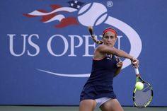 Monica Puig, of Puerto Rico, returns a shot to Zheng Saisai, of China,during the…