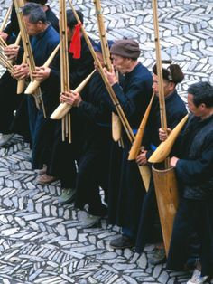 MIAO MEN PLAYING TRADITIONAL BAMBOO MUSICAL INSTRUMENT, CHINA