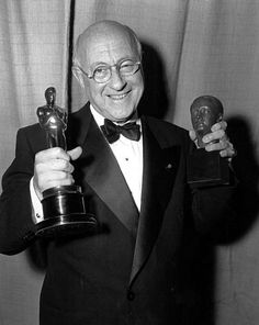 """Cecil B. De Mille poses in Los Angeles on March 19, 1953 at the 25th annual Academy Awards.  He holds his Oscar for best picture, """"The Greatest Show on Earth,"""" and the Irving G. Thalberg Memorial Award for consistently high production achievement. The 1953 Academy Awards were the first televised awards ceremony.  (AP Photo/stf)"""