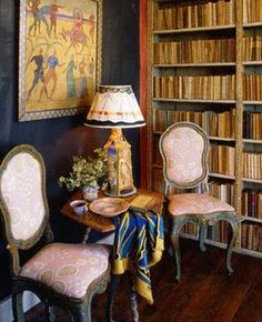 A small table and two chairs beside bookshelves at Charleston Farmhouse near    Lewes in East Sussex