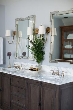 Elizabeth Reich - Breathtaking master bath boasts a chocolate stained oak double washstand fitted with cremone bolts topped with gray and white marble fitted with his and hers sinks tucked under Made Goods Norma Mirrors illuminated by brass wall sconces, Reed Sconces.