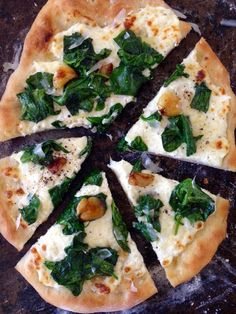 Ricotta Spinach Pizza Recipe, crispy thin rustic crust, creamy ricotta & gooey fontina, topped with sweet roasted garlic & sauteed spinach.