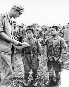 """(17 June 1945). Marine First Lieutenant Hart H. Spiegal of Topeka, Kansas, makes with the sign language as he tries to strike up a conversation with two tiny Japanese soldiers captured on Okinawa. The boy on the left is """"18"""" while his companion boasts """"20"""" years."""
