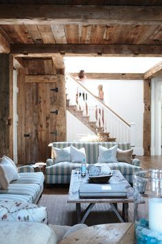 This rustic yet pretty summer cottage uses reclaimed wood timbers as support beams and for a wall feature that doubles as art. Combined with white painted beadboard the country look is clean and fresh.