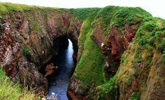 Bullers of Buchan, located in Buchan, Aberdeenshire, north-east coast of Scotland.  It is a collapsed sea cave where the sea rushes in through a natural archway.