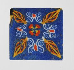 Square fragment of polychrome glass inlay: opaque yellow and white on blue ground, with a modern glass backing.  Width: 2.54 centimetres Greek & Roman Antiquities - 1878,1230.191 (Source: The British Museum)