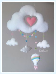 Móbile feito de feltro, costurado a mão e preenchido com fibra siliconada. Lindo móbile composto por uma nuvem com recorte em forma de coração, nuvenzinhas, bandeirolas e uma fofura de balão (Aproximadamente 15 cm de altura) . Sua leveza, o seu colorido e mobilidade traz calma e distração para...