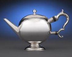 A rare and outstanding Scottish silver teapot by Edward Lothian. Crafted in an impressive bullet shape, this charming teapot features a dramatic, wood-insulated handle, subtle bright-cut engraving around the rim and hinged lid, and bears the armorial crest of the Gordon family of Cluny Castle, Scotland and Tobago.