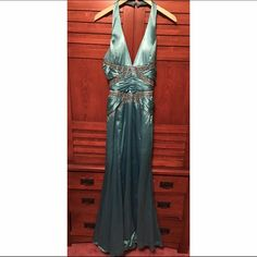 SALE Rivá Designs Strap Back Dress Size 12 Rivá Designs blue halter long dress with slit up the side. Backless with two rhinestone bead straps that cross, zips up the side. Slight amount of wear that is taken account for in the price. Size 12! Rivá Designs Dresses Prom