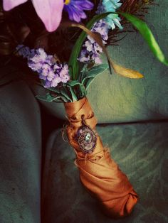 Fabric wrapped bouquet with brooch.... A great way to deal with holding those stems and also adding a pop of color!