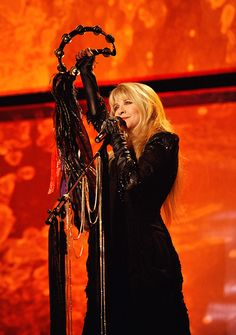 Stevie ~ ☆♥❤♥☆ ~ onstage, tamborine held high as she ends a song ~ stunning contrast between her all-black outfit and the red stage background Members Of Fleetwood Mac, Stevie Nicks Lindsey Buckingham, Stephanie Lynn, Stevie Nicks Fleetwood Mac, Look Vintage, Female Singers, Her Music, My Idol, Beautiful People