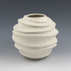 Modern vase {It has a very simple form but the outside is complex with the wave-like carvings/sculptures}