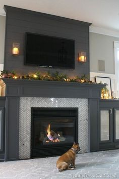 Dark grey built in fireplace with side cabinets.  Love the added height & visual interest with planks of wood above.  Herringbone tile inlay.