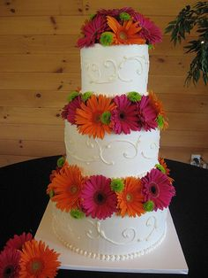Get a plain wedding cake and decorate yourself with flowers that go with your color scheme!