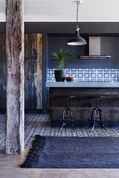 Masculine kitchen with exposed wooden beams, a reclaimed wood island, printed tile backsplash and an industrial pendant light