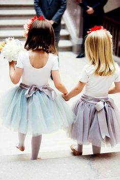 two flower girls with ballerina outfits and small bouquets