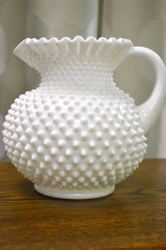 Fenton Hobnail Ruffled White Milk Glass Pitcher.  Hobnail glassware gets its name from the studs, or round projections, on the surface of the glass. These studs were thought to resemble the impressions made by hobnails, a type of large-headed nail used in bootmaking.  Fenton Art Glass introduced Hobnail Glass in translucent colors in 1939 & Milk Glass Hobnail in 1950