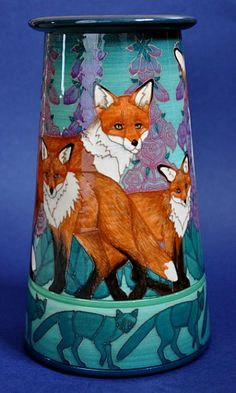 In Finnish mythology, the Aurora Borealis is known as Fox Fire or 'Revontulet', the curtains of coloured light being the sparks thrown up from it's tail as it brushes the icy snowfields. Foxgloves and a family of foxes feature in this beautiful design.    Revontulet is a Conical, hand thrown, hand decorated vase, approximately 23cm tall. It is designed for Illyria by Sally Tuffin and made in an edition of 10 by Dennis Chinaworks