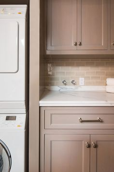 Small Laundry Room Features Taupe Cabinets Paired With White And Gray  Marble Countertops And A Taupe