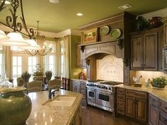 The green walls and ceiling with the dark rustic cabinets looks so refreshing!