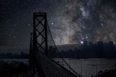 Night sky with silhouette of a bridge & cityscape
