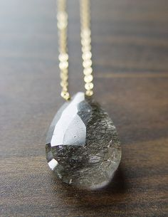 A gorgeous rutilated quartz necklace makes a bold statement. Its large size, pear shape, and intricate black rutilations puts it in a class of its