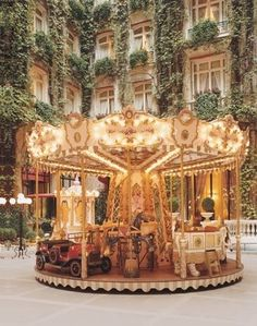 carousel in Paris. Seriously, look at that   building and those vines in the background...!! Must go.