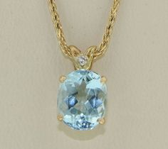 Aquamarine and diamond pendant set into an 18 karat yellow gold two level basket head, with a filigree bail,set with one round brilliant cut diamond .015ct VS FG. The Aquamarine is fine medium intense blue in colour and 2.56cts. in weight.