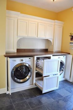 Front-loading washer/dryer set into a cabinet with doors that open and shut to reveal the pair. Drawers set in between.
