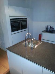 Wit glanzende greeploze keuken met spoeleiland en aparte kastenwand — in Eindhoven.