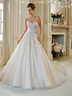 Gorgeous Tulle A-Line Wedding Ball Gown with Sweetheart Neckline, Fitted Bodice with Lace Applique and Crystal Hand-Beading into Skirt, Draped Sash at Natural Waist Accented with a Side Crystal Embellishment, Full A-Line Tulle Skirt into Chapel Train, Back Corset Closure.