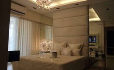 Master bedroom with high plush headboard design by Interior Designer: Shahen Mistry, India.