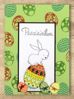 Valkoiselle kartongille on leimattu pupu ja pääsiäismuna ja sen yläpuolelle on leimattu Pääsiäisiloa. Pääsiäismuna on väritetty tusseilla. Kuva on liimattu mustalle paperille. Vaaleanvihreälle kort…