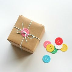 Use (handmade paper) buttons to wrap up a gift. Great site for gift packaging! Present Wrapping, Creative Gift Wrapping, Creative Gifts, Wrapping Ideas, Wrapping Papers, Baby Gift Wrapping, Birthday Gift Wrapping, Pretty Packaging, Gift Packaging
