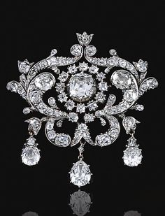 DIAMOND BROOCH, MID 19TH CENTURY. The central old-mine diamond in a cut-down collet within open work surrounds designed as foliate scrolls set with old-mine diamonds, suspending three pear-shaped diamond drops.