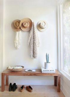 Um toque rústico habita este hall de poucos objetos - os tons terra colorem banco, sapato, chapéus e bowl